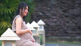 Беременная женщина отдыхая в саде акции видеоматериалы