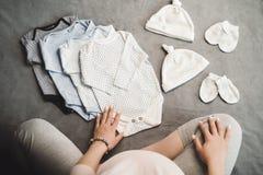 Беременная непознаваемая женщина сидя с одеждами младенца Взгляд сверху стоковые фото
