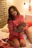 Беременность, люди и концепция ожидания - счастливая беременная женщина сидя на кровати и касаясь ее животу над праздниками стоковое фото