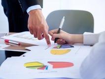 Бизнесмены обсуждая диаграммы и диаграммы показывая результаты их успешной сыгранности стоковые изображения rf