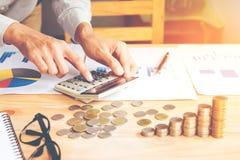 Бизнесмен в сером удерживании руки рубашки, вычислении с калькулятором и финансовых данных анализируя и рассчитывая на калькулято стоковое фото rf