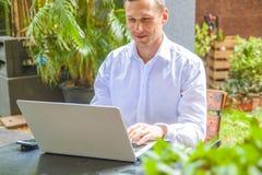 Бизнесмен в рубашке сидит в кафе и работает с ноутбуком на отдыхе. stock photo