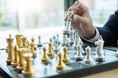 Бизнесмен играя диаграмму шахмат принимает мату другого короля с командой, выигрышем стратегии или управления или концепцией успе стоковые фотографии rf