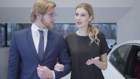 Бизнесмен и женщина между строками новых электрических автомобилей в мотор-шоу выбирая одно для покупки Пары обнимая, вокруг мног сток-видео