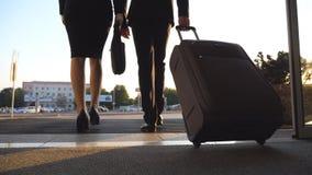Бизнесмен и женщина при багаж идя от авиапорта к улице города Следовать к чемодану нося молодого бизнесмена видеоматериал