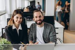 Бизнесмен и коммерсантка работая с компьтер-книжкой на современном офисе стоковое изображение rf