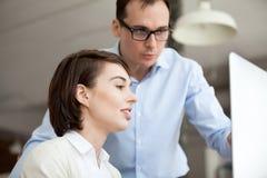 Бизнесмен и коммерсантка работая совместно используя компьютер стоковые изображения rf