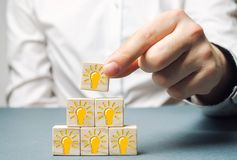 Бизнесмен кладет деревянные блоки с электрической лампочкой идеи или воодушевленности Поколение новаторских идей дела творческо стоковые изображения rf