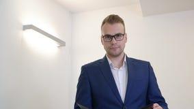 Бизнесмен портрета молодой смотря папку документа в офисе сток-видео