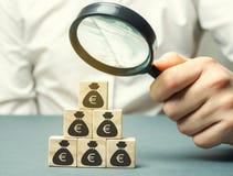 Бизнесмен держит лупу над кубами с евро Анализ выгод и доходов в компании Распределение денег стоковое фото rf