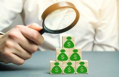 Бизнесмен держит лупу над кубами с долларами Анализ выгод и доходов в компании Распределение денег стоковое фото rf