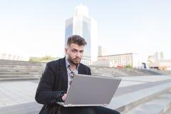 Бизнесмен сидя на улице, работая на ноутбуке и смотря в камеру стоковое изображение