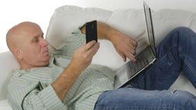 Бизнесмен с ноутбуком лежа удобно на электронных почтах мобильного телефона проверки софы стоковые фотографии rf