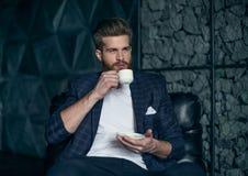 Бизнесмен с чашкой кофе распологая против современной предпосылки стоковое фото rf