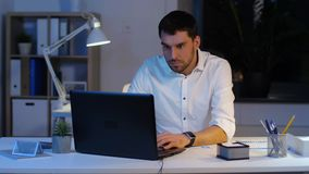 Бизнесмен с офисом ноутбука и бумаг вечером видеоматериал
