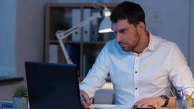 Бизнесмен с офисом ноутбука и бумаг вечером акции видеоматериалы