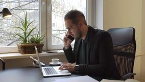 бизнесмен работая на ноутбуке в офисе звоня телефонный звонок нервный и сердитый сток-видео