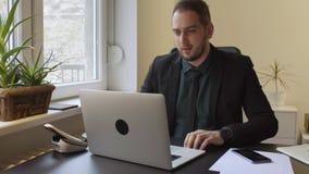 бизнесмен работая на ноутбуке в офисе звоня телефонный звонок нервный и сердитый видеоматериал