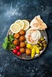 Ближневосточный диск meze с falafel, питой, hummus, соленьями, редисками Среднеземноморская или греческая идея партии закуски стоковое изображение rf