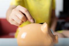 Близкая поднимающая вверх правая рука женщины кладя одну монетку в копилку стоковая фотография rf