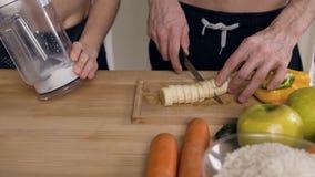 Близкая поднимающая вверх съемка мужских рук отрезая банан и женских рук смешивая молоко в смесителе в кухне сток-видео