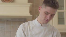 Близкий поднимающий вверх портрет молодого сконцентрированного повара в форме шеф-повара подготавливая еду дома в кухне концепция сток-видео