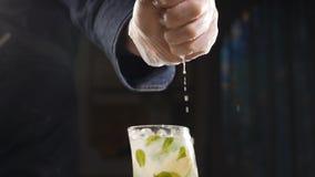 Близкий поднимающий вверх шеф-повар руки сжимая известку на свежий коктейль mojito в замедленном движении сок капая из плода Мыжс сток-видео