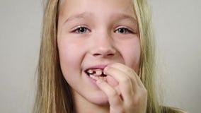 Близко - вверх милой усмехаясь девушки, младенца маша клык молока пальца внутри помещения с белой предпосылкой Потеря зуба концеп сток-видео
