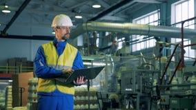 Блок завода производящ химикаты с мужским работником работая ноутбук видеоматериал