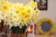 Букет желтых и белых daffodils в вазе на предпосылке свечи, желтой плиты с тюльпанами и картины стоковая фотография rf