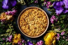 Букет ярких цветков и яблочного пирога лежа на серой предпосылке Плоское положение Взгляд сверху стоковое изображение