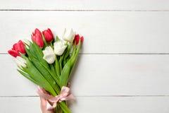 Букет тюльпанов на белом деревянном столе, космосе экземпляра для текста Модель-макет на праздники весны, Inte знамени приглашени стоковое фото rf