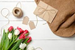 Букет цветков тюльпанов, конверт kraft, шпагат, бирки, мешковина на белом деревянном столе Винтажная поздравительная открытка на  стоковая фотография rf