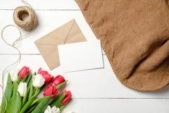 Букет цветков тюльпанов, конверт kraft, шпагат, мешковина на белом деревянном столе Винтажная поздравительная открытка на день же стоковые изображения
