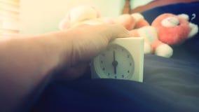 Будильник 6 часов в утре на кровати дома Концепция предпосылки утреннего времени, мягкий фокусировать и винтажный стиль цвета стоковое изображение rf