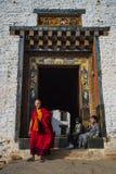 Буддийский монах держит его книгу мантры и приходит вне от ворот Dzong, Trashigang Dzong, восточного Бутана стоковое изображение