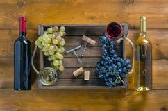 бутылки 2 вина и виноградин на деревянной предпосылке стоковое фото rf