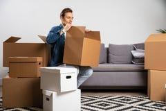 Брюнет с картонной коробкой в руках стоя в квартире стоковое изображение rf