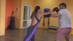 Бой человека и женщины шутя в перчатках бокса в спортзале, замедленном движении сток-видео