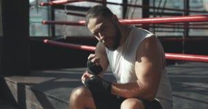 Боксер сидя на крае боксерского ринга глубоко в мысли после для разработки в туманном спортзале сток-видео