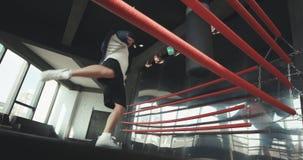 Боксер ударяет грушу в спортзале в замедленном движении Молодой человек тренируя внутри помещения Сильный спортсмен в спортзале и видеоматериал