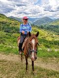 Более старая женщина верхом, в холмах вне Vilcabamba, эквадор стоковая фотография