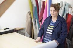 Более старая женщина в фабрике мебели подготавливает серый материал для измерять и резать стоковая фотография