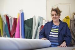Более старая женщина в фабрике мебели подготавливает серый материал для измерять и резать стоковые фото