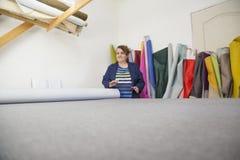 Более старая женщина в фабрике мебели подготавливает серый материал для измерять и резать стоковые изображения rf