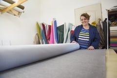 Более старая женщина в фабрике мебели подготавливает серый материал для измерять и резать стоковая фотография rf