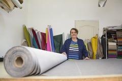 Более старая женщина в фабрике мебели подготавливает серый материал для измерять и резать стоковое фото rf