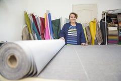 Более старая женщина в фабрике мебели подготавливает серый материал для измерять и резать стоковое изображение rf