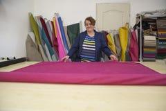 Более старая женщина в фабрике мебели подготавливает розовый материал для измерять и резать стоковое фото