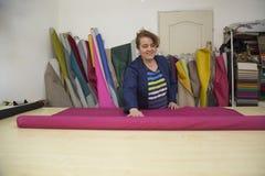 Более старая женщина в фабрике мебели подготавливает розовый материал для измерять и резать стоковая фотография rf